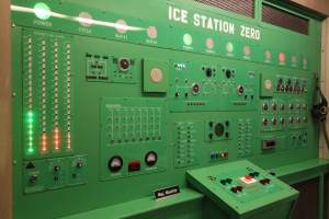 "In-game: A very large green computer with many lights, buttons, and switches. It is labeled, ""Ice Station Zero."""