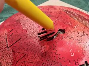 A pen with a sticky tip being used to extract a piece shaped like an alien from the assembled puzzle.