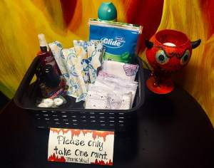 A basket with floss, maxipads, tampons, mouthwash, and mints in a bathroom.