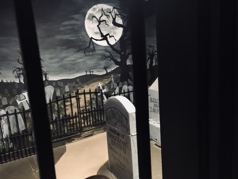 In-game: View of a a cemetary through a metal gate.