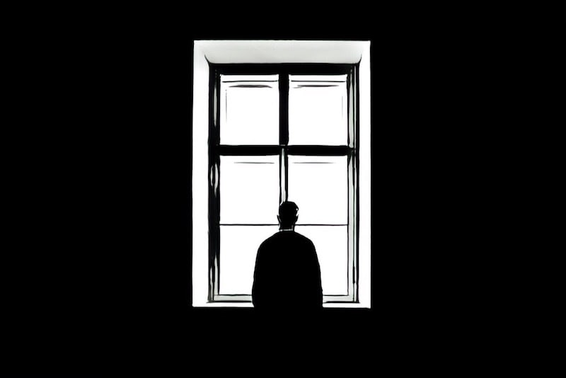 Black & White, a lone person looking out a large window from behind.