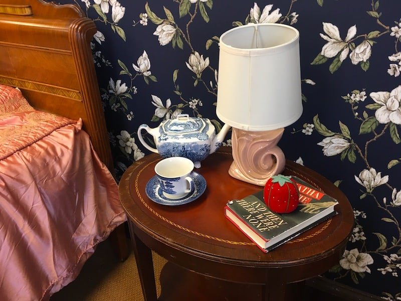 In-game: closeup of a nightstand with a book, a lamp, a tea pot and a tea cup.