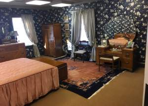 In-game: Wide view of a bed room with large dressers and a makeup vanity.