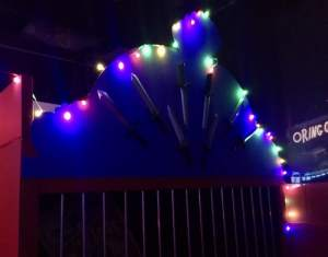 In-game: A cage decorated with knives and lit with a string of lights.
