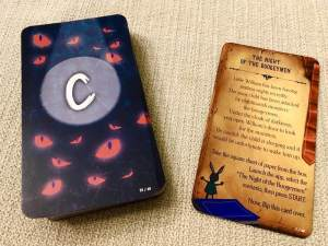 A stack of player cards on the left, the card backs are covered with glowing red eyes beside a story card explaining that a child is being hauned by monsters at night.