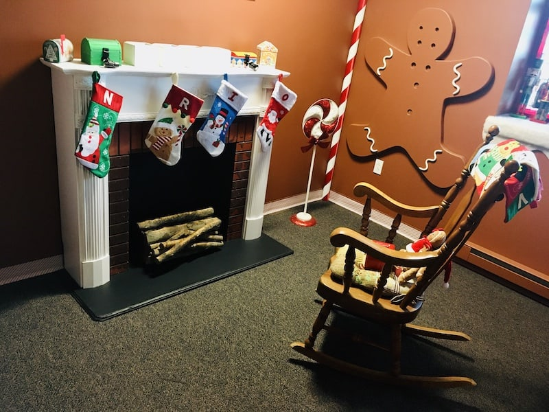 In-game: A fireplace decorated with stockings, a rocking chair, and a giant - partially decorated gingerbread cookie on the wall.