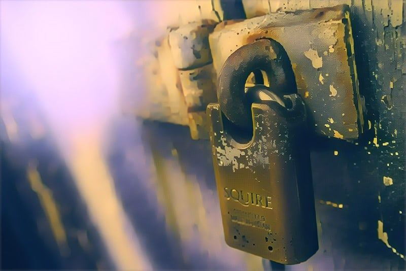 Closeup of a beefy squire padlock securing a door.