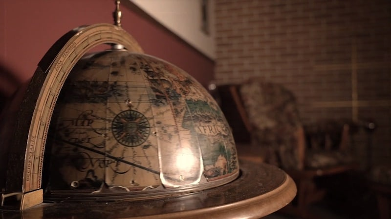 In-game: closeup of a globe in a study.