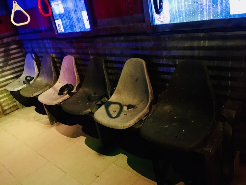 In-game: seats of an old, rundown subway.