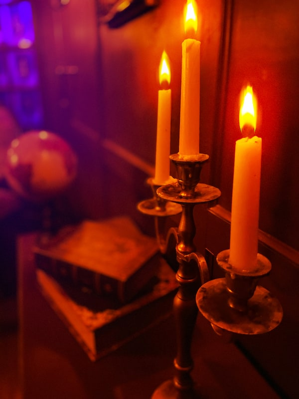 Close-up of a lit candelabra with books and a globe visible in the background.
