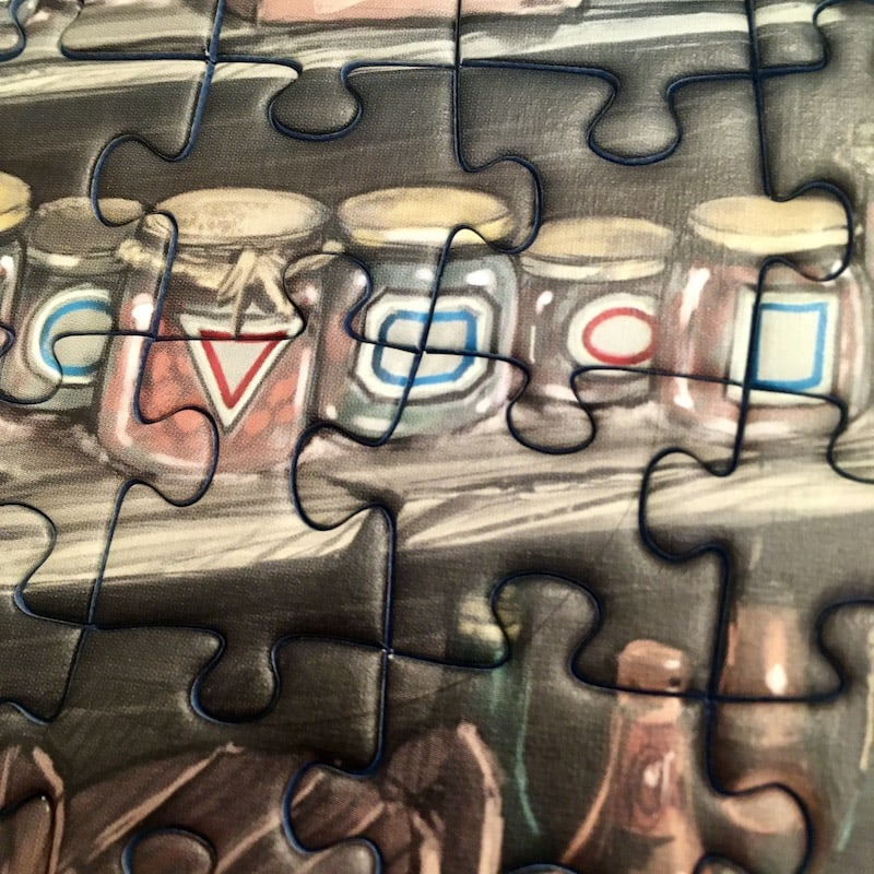 Portion of the puzzle - a closeup of a set of jars with red and blue shapes as labels.