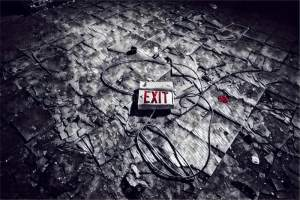 An exit sign ripped down land laying in the middle of the floor.