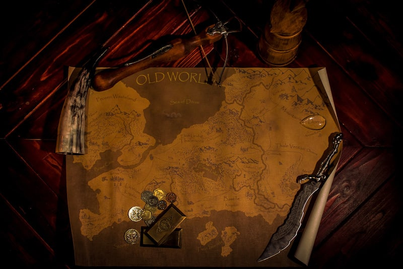 In-game: a map of a fantasy land surrounded by gold, and weapons.