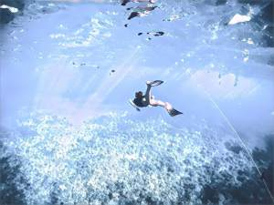 A swimmer with fins free diving under water.
