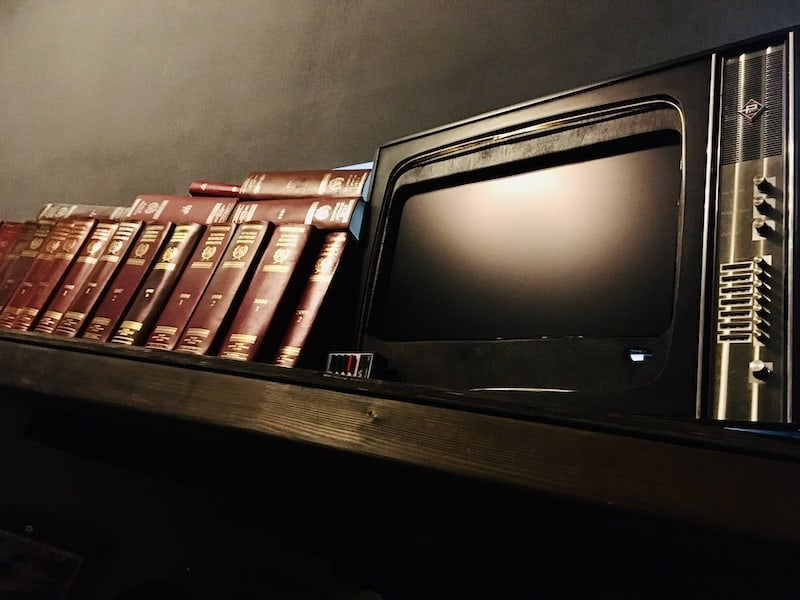 In-game: Closeup of a bookshelf with an old CRT television resting on it.