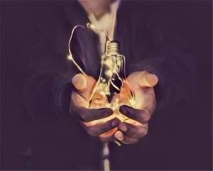 A hand holding an illuminated light bulb.