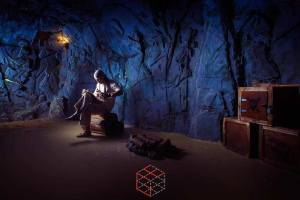 In-game: A man sitting on a rock in a cave.