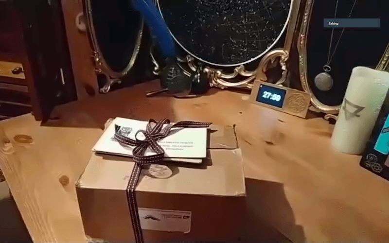 A sealed box on a table surrounded by magical props.