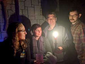 Post game photo - the team looking into a candle in a dungeon.