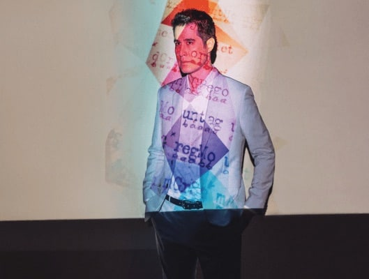 David Kwong of the Enigmatist with a image projected on top of him.