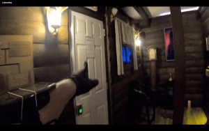 A black gloved hand pointing at a door inside of a cabin.