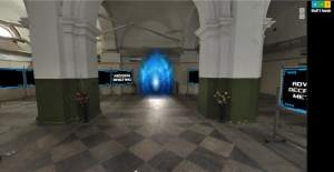 """A large hallway with tall ceilings and lage pillars. Across the way is a screen that reads """"Mission Briefing"""" beside a big, glowing, blue portal."""