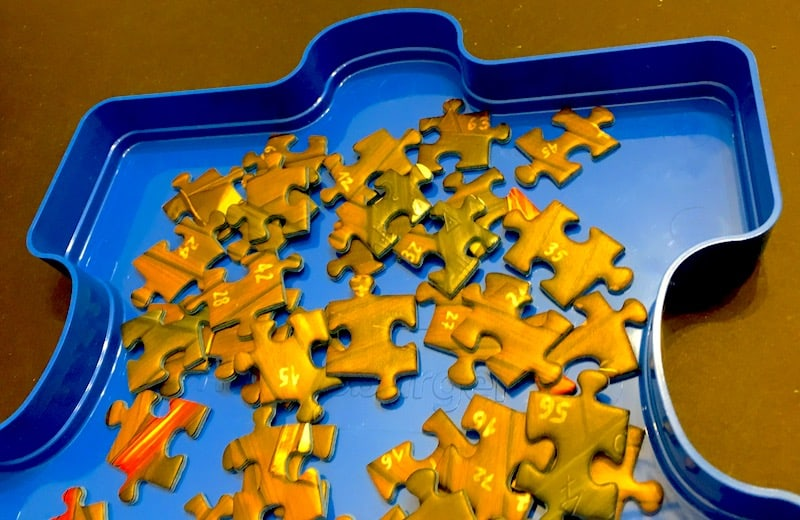 Traditional cardboard jigsaw puzzl pieces in a tray shaped like a blue puzzle piece.
