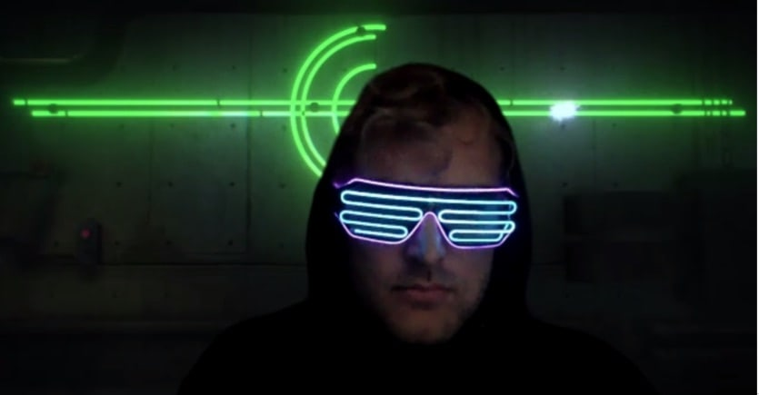 A person in a cyber-punk scene whereing neon goggles, obscuring his identity.