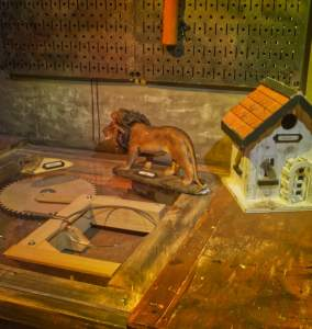 Zoom view of a workbench with a model house, a statue of a lion, and a strange mechanical contraption.