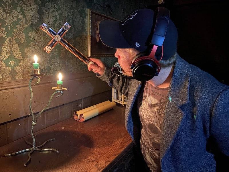 A person wearing a headset investigating a cross.