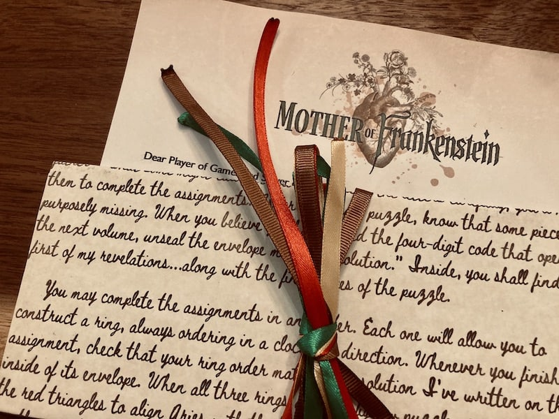 A welcome letter tied off with red, green, and brown ribbon.