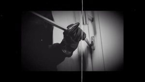 Image of a gloved hand using a crowbar on a door.