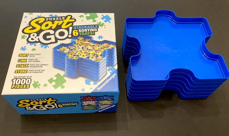 Puzzle Tray packaging beside a stack of trays.