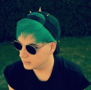 Headshot of Joel with sunglasses and green hair