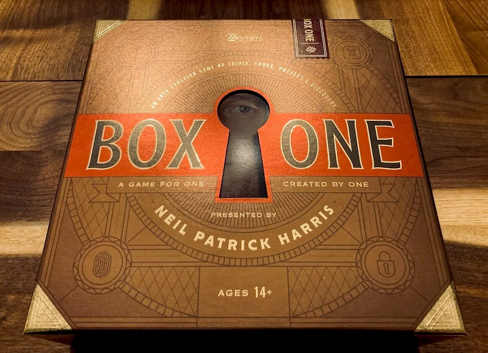 Red, black,and gold, with NPH's eye peering through a keyhole Box One packaging