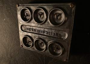 """In-game: Closeup of a set of 6 metal switches in a pitted metal box labeled """"Hever Iron Works."""""""