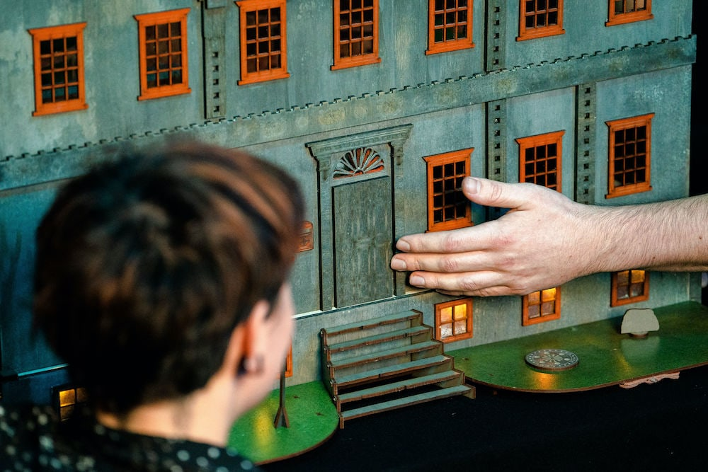 A hand gently caressing the dollhouse while someone watches.