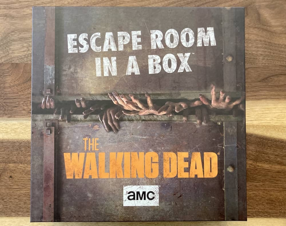 Escape Room in a Box The Walking Dead box art depicts a cracked door with many zombie hands reaching through it.