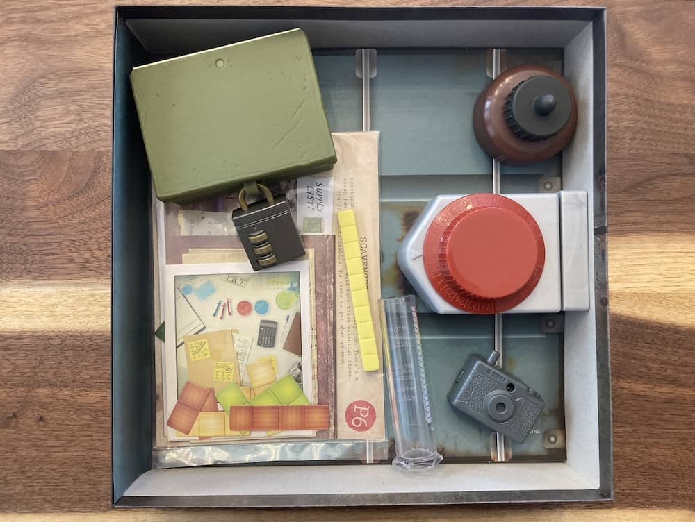 Open box, an assortmnt of locks, paper puzzles, and plastic props.