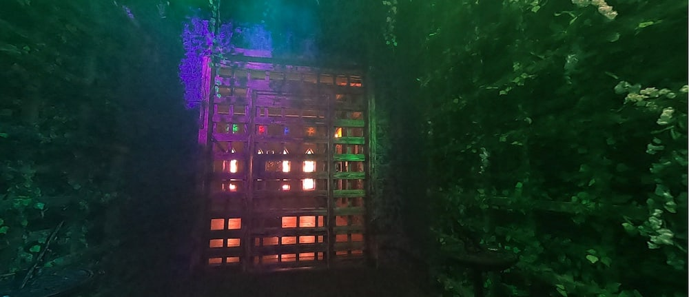 A caged door with glowing lights beyond it.