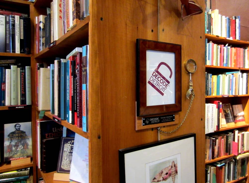 A packed bookshelf with a framed Decode logo attached to the side.