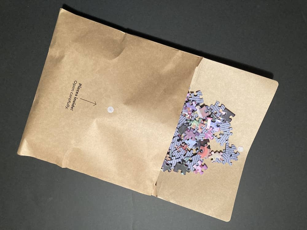 Puzzle pieces being poured from a paper envelope.