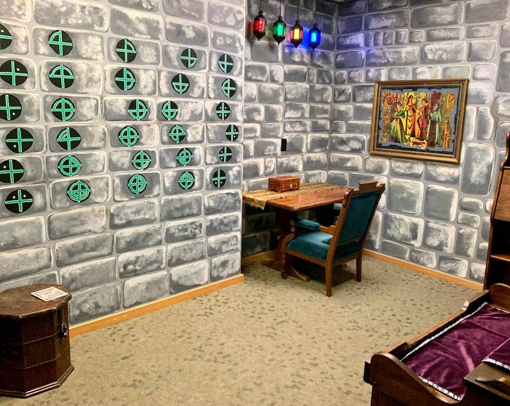A wizard's study with sigils on the stone wall.