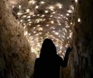 A woman in black walking through a dramatically lit cave.