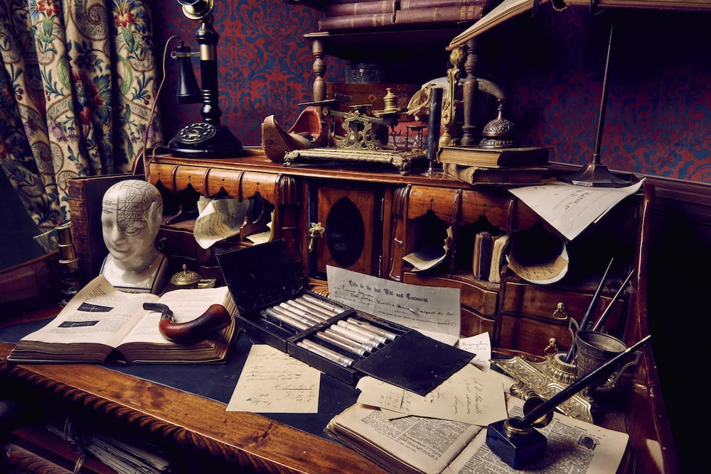 A beautiful old desk covered in documents, artifacts, and a pipe.