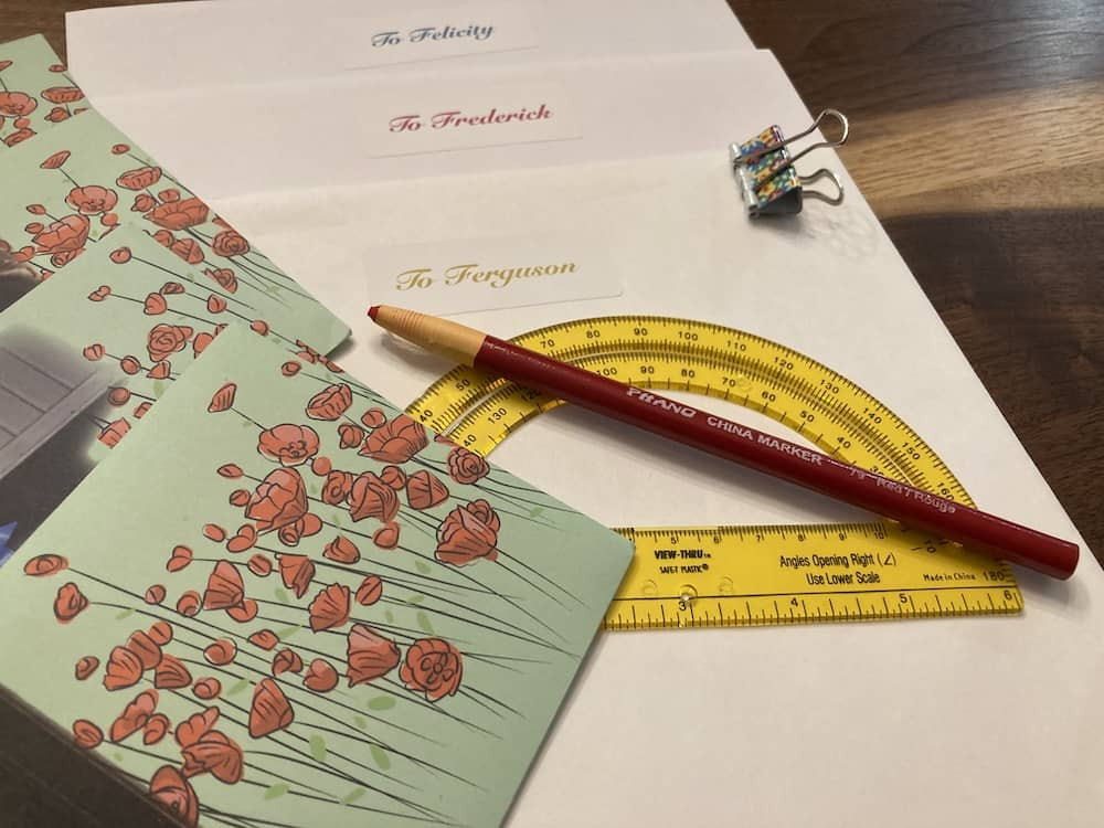 A protractor, grease pen, and assorted envelopes, each with a different name on it.