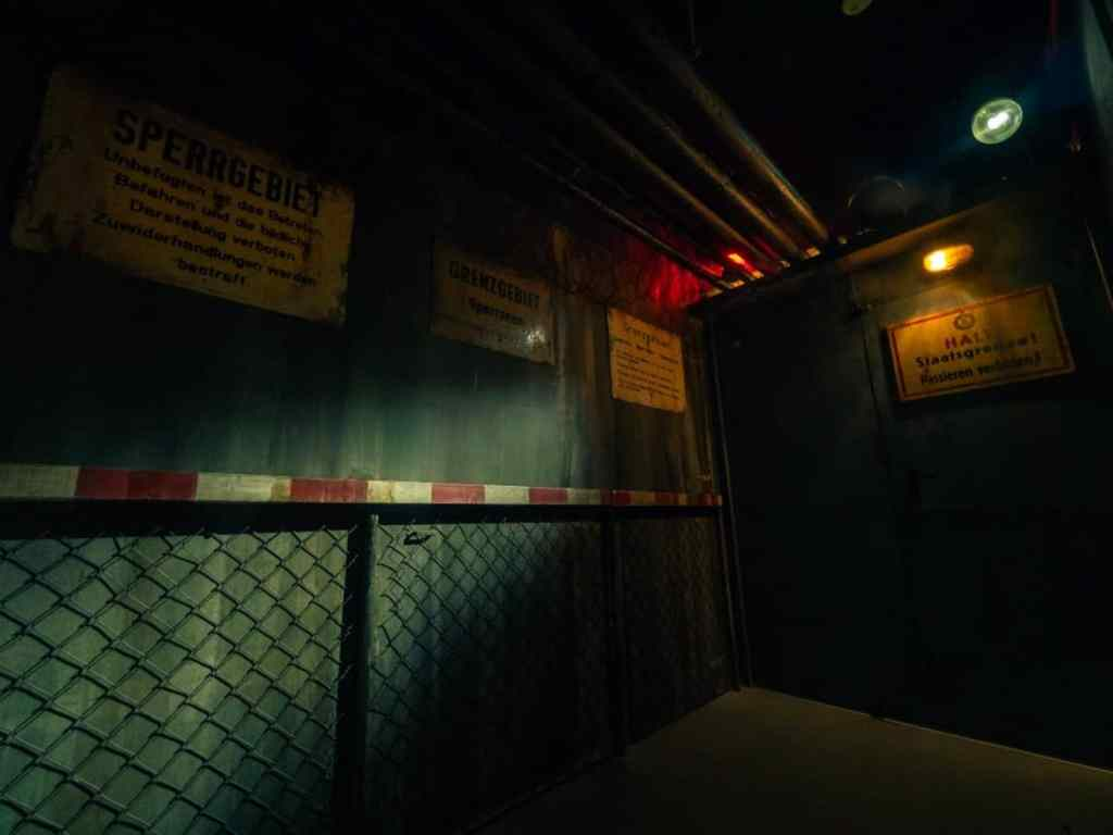 dark room with german signs on the wall and chain link fencing