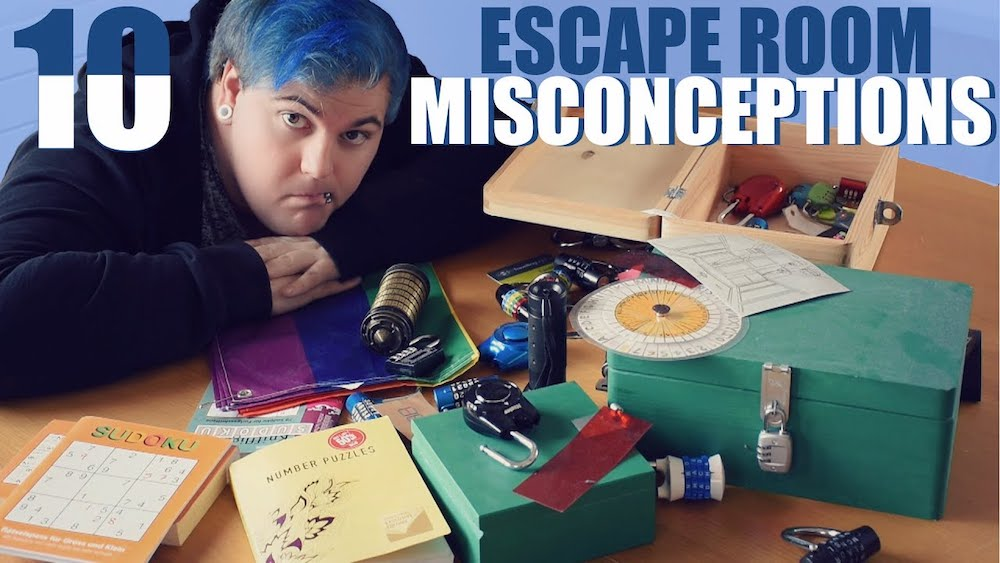 """Joel with blue hair leaning over a table covered in locks, puzzles, and boxes. Labeled, """"10 Escape Room Misconceptions."""""""