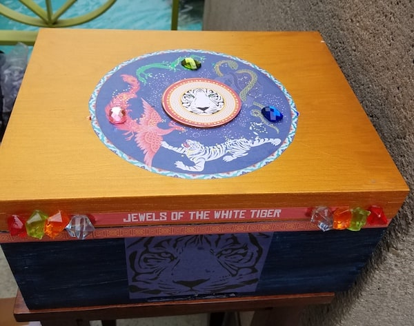 """A wooden box labeled """"Jewels of the White Tiger,"""" decorated with colorful plastic jewels and images of the four celestial guardians."""