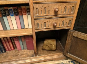 Closeup of an old desk, with an open cabinet and a puzzle within.